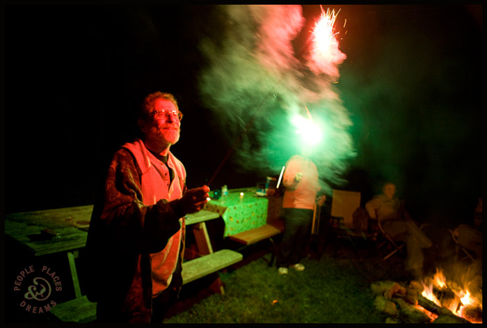 Sid Kaplan holding a sparkler at night.